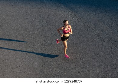 Attractive woman athletic fitness model doing jogging and workout in the morning time on a sunny summer day. Concept of attractive body and fitness workouts. Copyspace