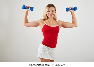 Attractive woman with athletic slim body is holding dumbbells in her hands isolated over white background