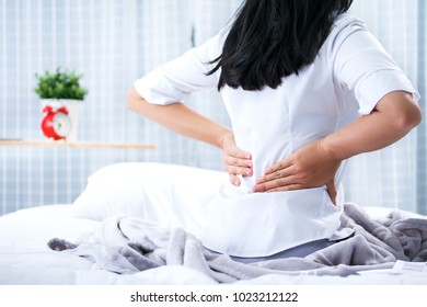 Attractive woman with back pain at home in the bedroom  Medicine and health care concept.