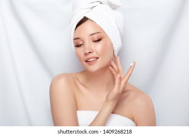 attractive woman in bath towel applying cream on her face isolated on white, pure and fresh young girl doing spa procedures