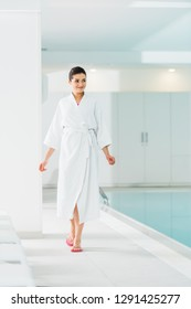 attractive woman in bathrobe walking near swimming pool