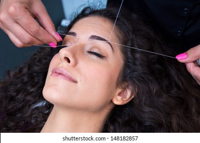 attractive woman in beauty salon on facial hair removal eyebrows threading procedure