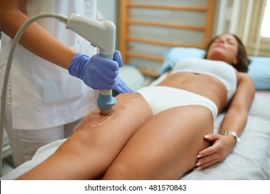 attractive woman in beauty salon on localized anti fat treatment therapy on the thigh