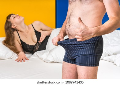 Attractive woman in bed and man in underwear is looking inside and is showing thumb up - impotence concept