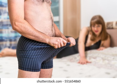 Attractive woman in bed and man in underwear is looking inside - impotence concept