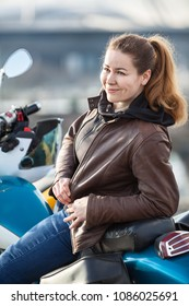 Attractive woman biker sitting on her motorcycle, leather brown jacket and jeans