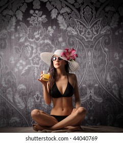 attractive woman in bikini drinking a cocktail on tapestry background