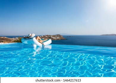 Attractive woman in bikini floats on a infinity swimming pool with view to the mediterranean sea in Greece during summer time