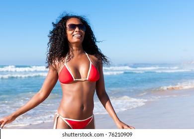 Attractive Woman in bikini standing in the sun on beach with sun glasses