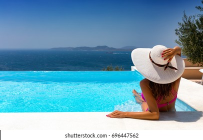 Attractive woman in bikini and with white hat is relaxing in an infinity pool