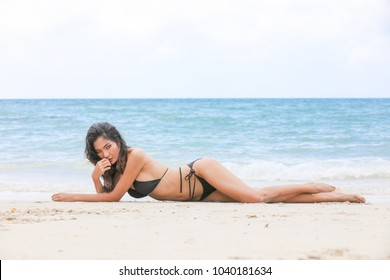 Attractive woman in black bikini with perfect body relaxing on a sand at beautiful beach with copyspace.