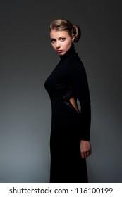 attractive woman in black dress posing over dark background