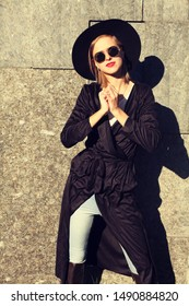 attractive woman in black trench suede coat, wool hat and round glasses, artsy bohemian style, fashion blogger outfit