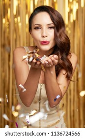 Attractive woman blowing out confetti in her hands