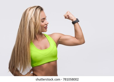 Attractive woman in bright sports bra showing her biceps on white background.