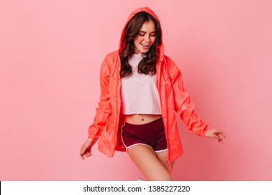 Attractive woman in bright windbreaker with smile posing in pink studio on isolated background
