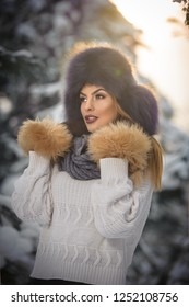 Attractive woman with brown fur cap and jacket enjoying the winter. Side view of fashionable blonde girl posing against snow covered bridge. Beautiful young female with cold weather outfit