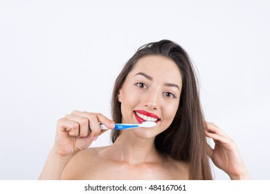 attractive woman brushing teeth on white background