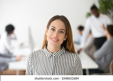 Attractive woman business leader smiling looking at camera headshot portrait, beautiful elegant businesswoman, successful professional female boss or company executive manager coach posing in office