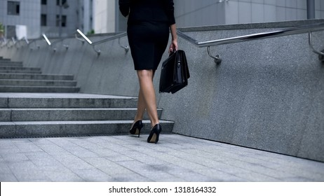 Attractive woman in business suit walking upstairs, concept of successful career