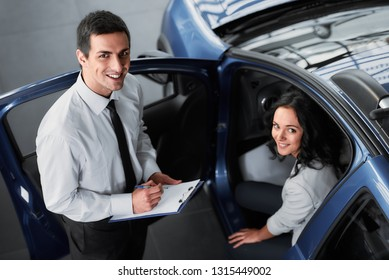 Attractive woman at car salon with consultant choosing a car.
