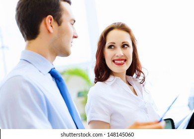 Attractive woman at car salon with consultant choosing a car
