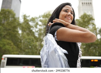 An attractive woman carrying a professionally laundered shirt over her shoulder.