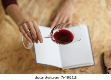 Attractive woman check red wine in white paper background.