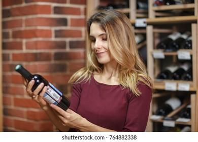 Attractive woman choose wine in the cellar.