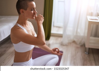 Attractive woman with closed eyes practicing nadi shodhana pranayama (Alternate Nostril Breathing) at home on purple mat. Side view, background window