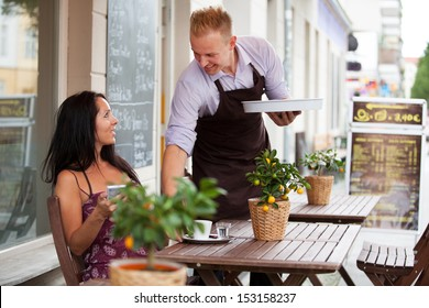 Attractive woman in a coffee shop and a smiling waiter