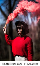 Attractive woman with a colorful smoke cloud grenade bomb fashion glitter