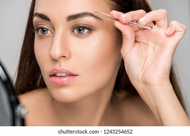 attractive woman correcting shape of eyebrows with tweezers isolated on grey