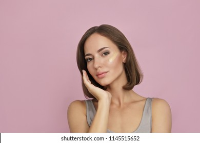attractive woman with cosmetic foundation on skin on pink background