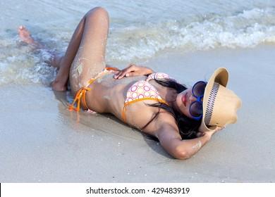 Attractive woman with cowboy hat lying on the sea beach. Girl in a bikini lying on a sea beach. Girl in a sexy swimsuit relaxes with hat on the beach. Provocative girl in a bikini wash sea waves.