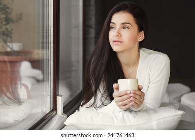 Attractive woman with a cup of coffee on the bed. Beautiful Girl Drinking Tea sitting in front of the window Indoor. Woman with the Cup of Hot Beverage.