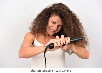 Attractive Woman with Curly Hair and Long Straight Hair Using Hair Straightener. Cute Smiling Girl Straightening Healthy Brunette Hair with Flat Iron