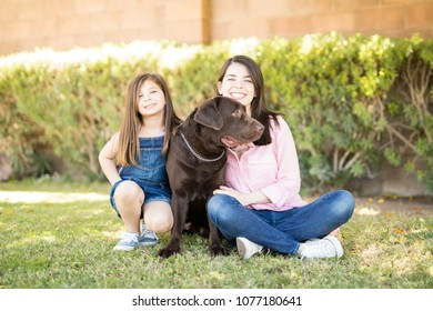 Attractive woman and cute little girl sitting with chocolate labrador pet dog sitting in center.