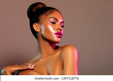 Attractive woman Dark Skinned с Sexy lips. fashion portrait Vivid Pink makeup. Beauty. fashionable Wet make-up в Pink tones. lighting pink filter light.- image.