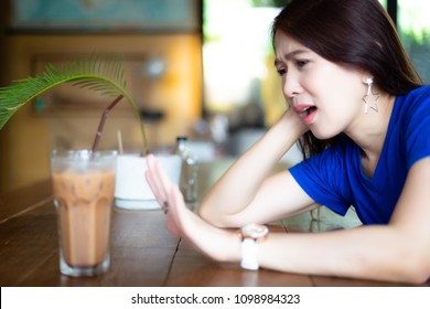 Attractive woman deny to drinking ice coffee because it's not good for health. It has a lot of caffeine and pretty young woman wants to diet. Gorgeous girl afraid of getting obese or fat. copy space