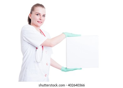 Attractive woman doctor smiling with a big box on her hands with advertising area isolated on white