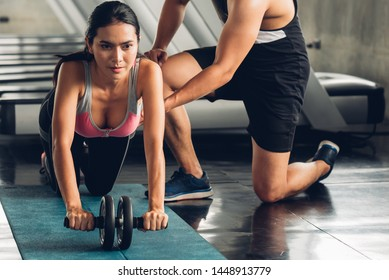 Attractive woman doing exercise with personal trainer at gym.