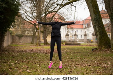 attractive woman doing jumping jack exercises in park during winter. old castle in the background.