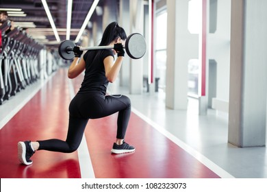 Attractive woman doing lunge exercise with barbell load on back