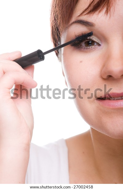 attractive woman doing makeup. over white background