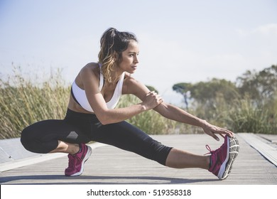Attractive woman doing stretching exercises outdoors