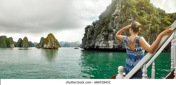 attractive woman in a dress is traveling by boat in Halong Bay. Vietnam.Travel to Asia, happiness emotion, summer holiday concept