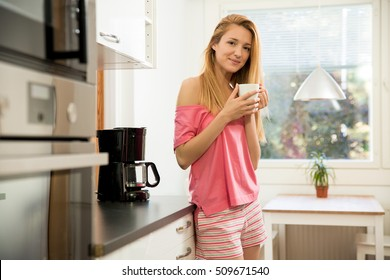 Attractive woman dressed in pyjamas in the kitchen pouring a mug of hot filtered coffee from a glass pot. Having breakfast in the morning