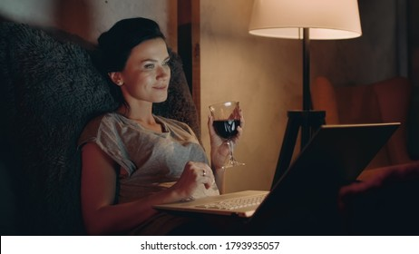 Attractive woman drinking red wine with notebook in night room. Closeup smiling woman relaxing with glass of wine at home. Pretty girl looking laptop with wineglass on couch.