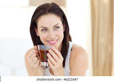 Attractive woman drinking tea sitting on her bed